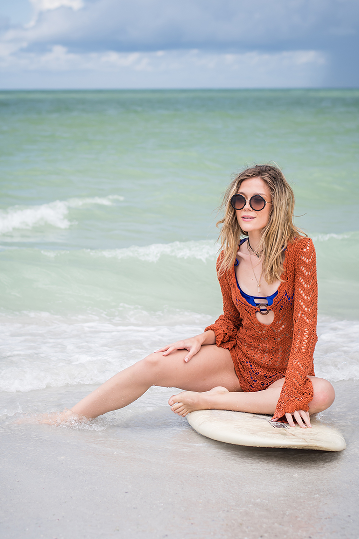 woman on the beach sitting on a surfboard